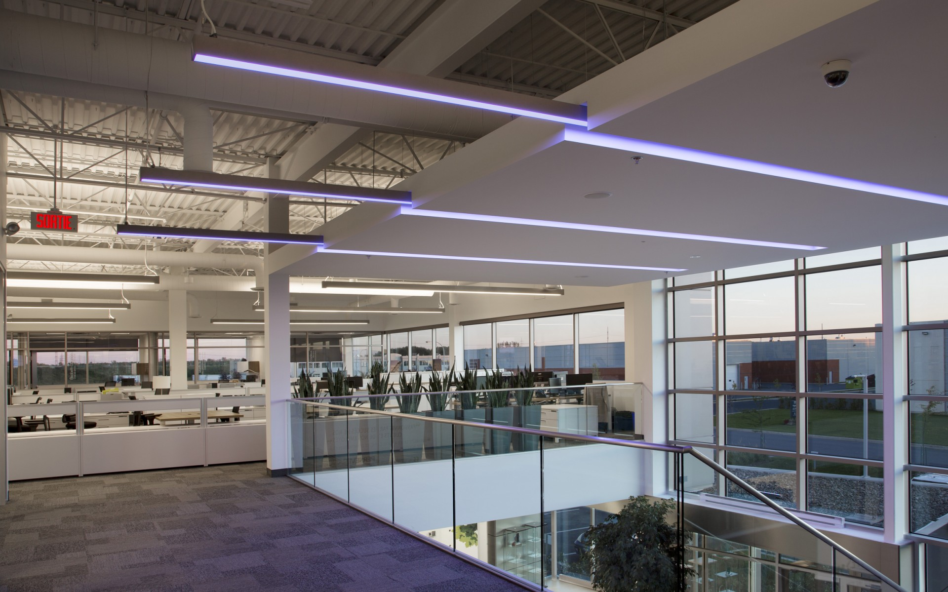 Beyond the atrium, open plan office spaces are lit with Lumenline Pendant Direct/Indirect luminaires.