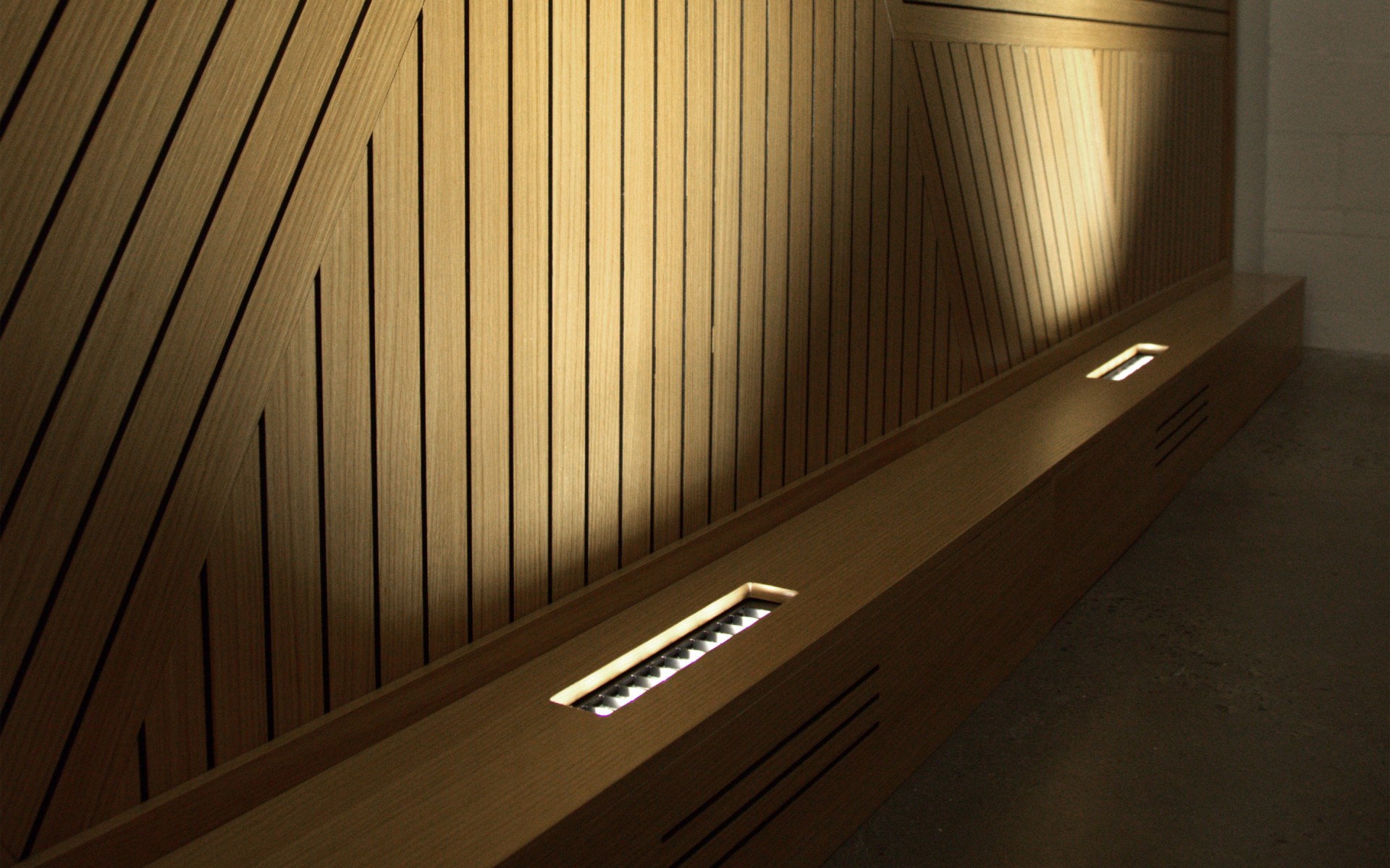 The wood paneling in the open office area is uplit using Lumenfacade luminaires.