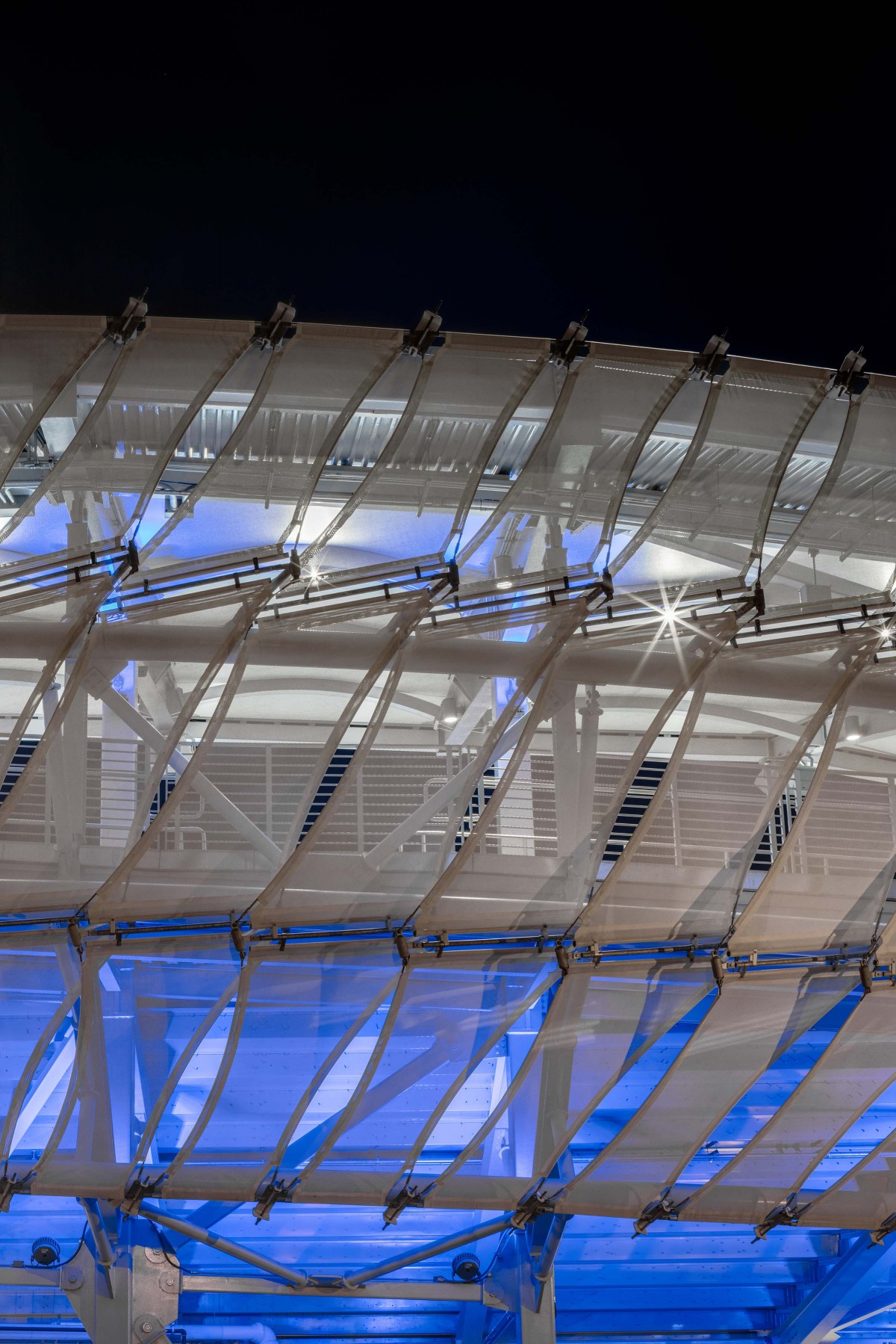 These panel materials play with opacity and translucence, offering glimpses in and out of the stadium. – Rafael Gamo